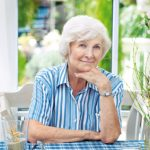 Seniorin sitzt entspannt im Wintergarten, im Hintergrund der Garten