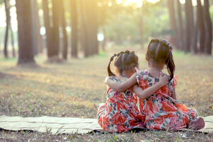 backside of two girls sitting and hug together in the park in vintage color tone