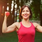 Portrait of cheerful aged woman in fitness wear exercising with red dumbbells in park.