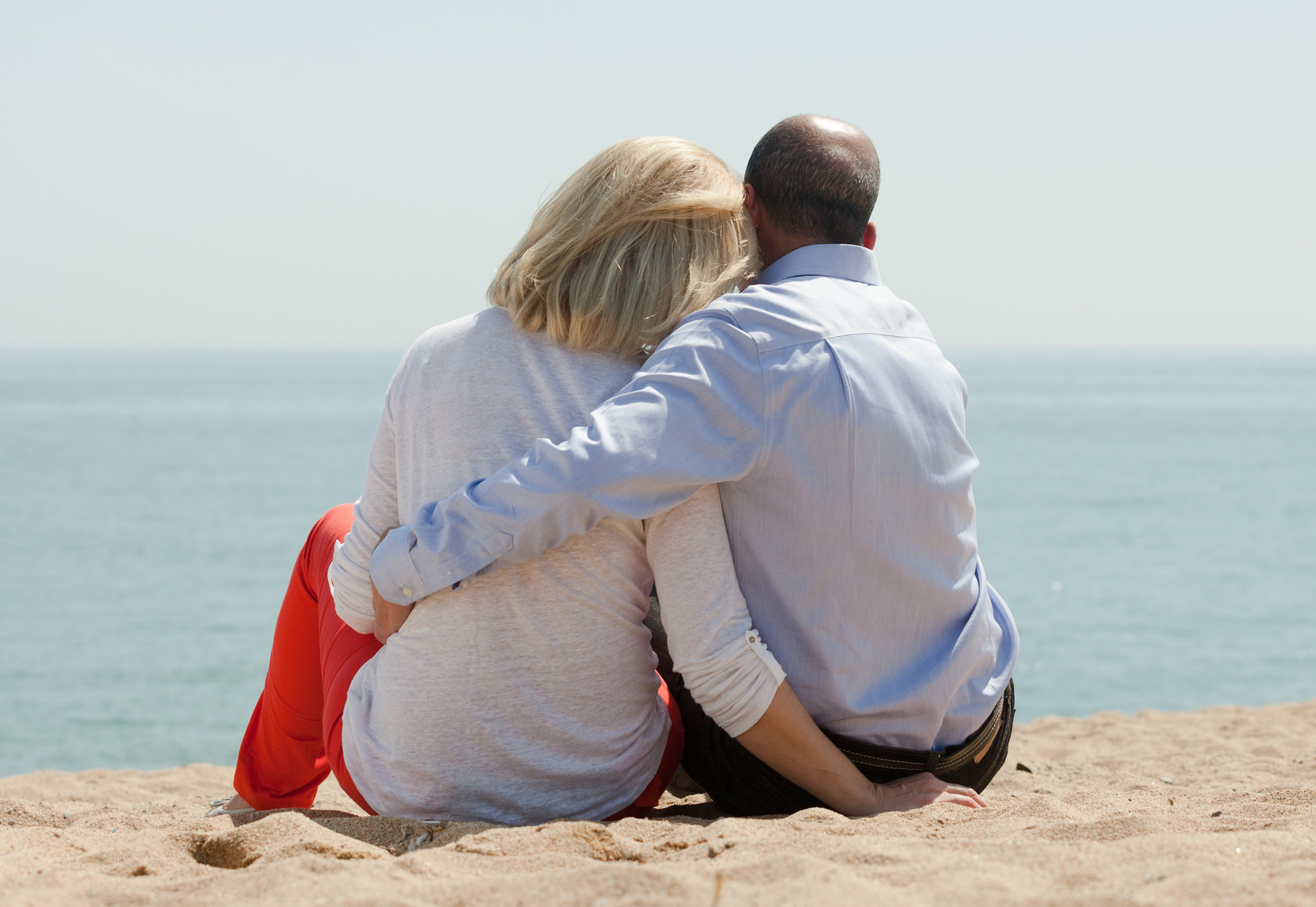 Mature lovers sitting on sand at beach and enjoying the view