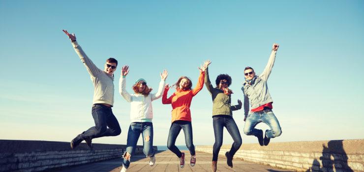 Glückliche Gruppe von Freunden, die vor Freude in die Luft springen